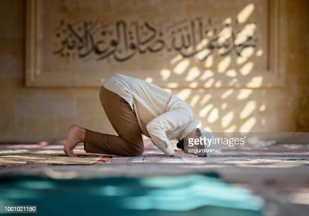 muslim man is praying in mosque - mosque stock pictures, royalty-free photos & images