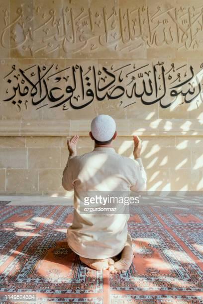 muslim man is praying in mosque - koran stock pictures, royalty-free photos & images