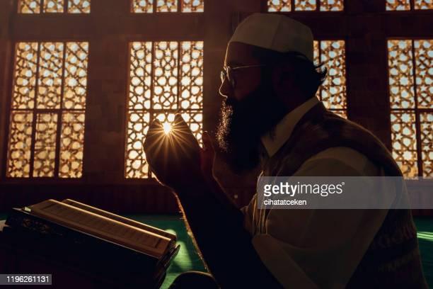 moslim man is aan het bidden in de moskee - moskee stockfoto's en -beelden