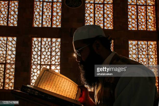 muslim man is reading the quran in the mosque - religious text stock pictures, royalty-free photos & images