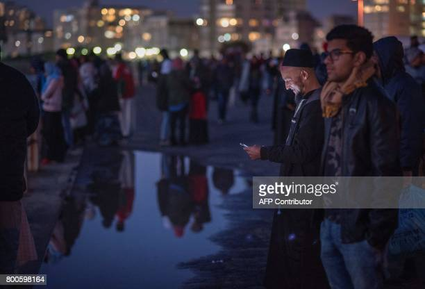 A Muslim man looks at his telephone as others look out to sea after the evening prayer at Three Anchor Bay in Cape Town on June 24 as Islamic leaders...