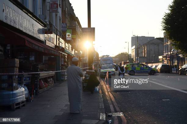 Muslim man looks on as police officers guard a road leading to an incident in which a van hit worshippers near Finsbury Park Mosque on June 19 2017...