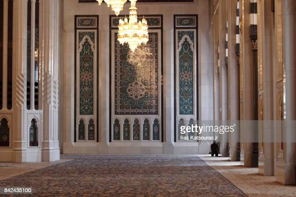 A muslim man prays in the main hall of the Sultan Qaboos Grand Mosque, Muscat, Oman