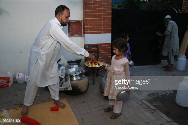 Muslim man prepares a plate for a little girl at the iftar dinner on the first day of holy Islamic month of Ramadan in Islamabad Pakistan on May 17...