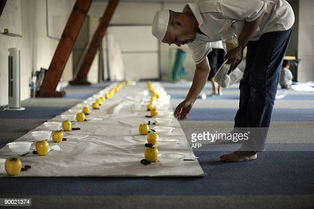 A muslim man prepares the table for the breaking of the fast at the AnNour mosque on the first day of the holy fasting month of Ramadan in Mulhouse...