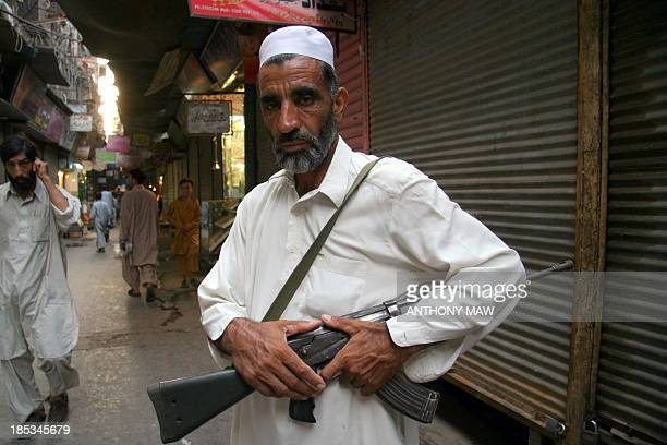 Muslim man proudly shows off his modern Hungarianmade AK47 automatic assault rifle down the streets of Peshawar in the Northern Areas District The...