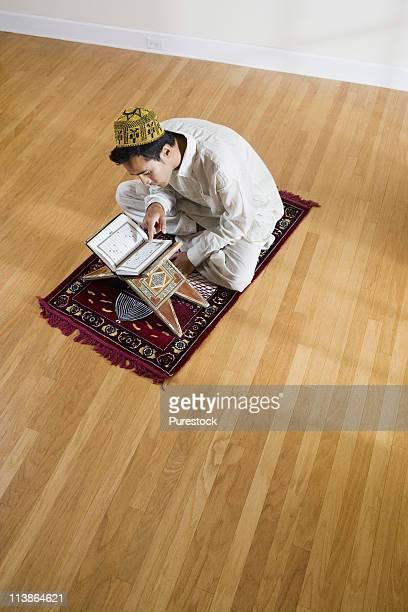 A Muslim man reading Koran on a prayer mat