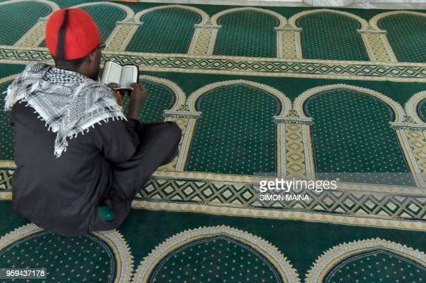A Muslim man reads from the Koran at a Mosque in Nairobi on May 17 2018 during the first day of the Islamic holy month of Ramadan
