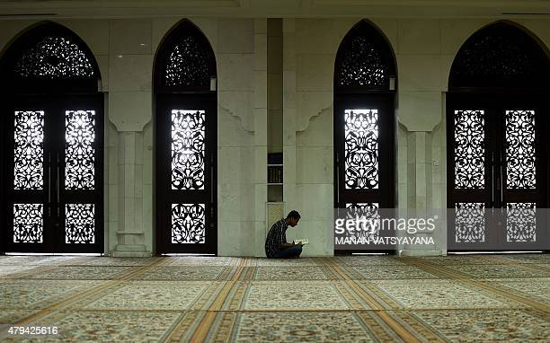 A Muslim man reads the koran at a mosque during the Islamic month of Ramadan in Kuala Lumpur on July 4 2015 on the day of Nuzul AlQuran which...