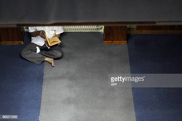 A Muslim man reads the Koran Islam's holiest book at the AnNour mosque on the first day of the holy fasting month of Ramadan in Mulhouse on August 22...