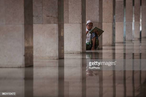 A Muslim man reads the Quran at the Istiqlal Mosque in Jakarta Indonesia on May 25 2018 Muslims around the world celebrate the holy month of Ramadan...