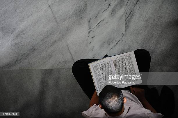 Muslim man reads the Quran on the second day of Ramadan while waiting to breaking the fast time at Al Akbar Mosque on July 11 2013 in Surabaya...