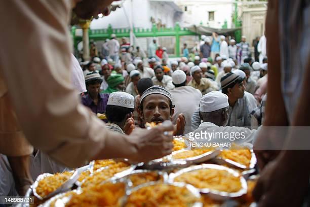 A Muslim man receives a plate of biryani rice as he and others prepare to break their fast on the first day of the holy month of Ramadan at the...