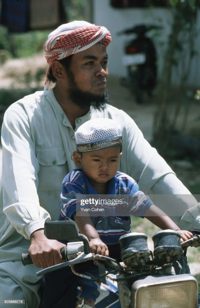 a muslim man riding a motorcycle with his son in pattani town