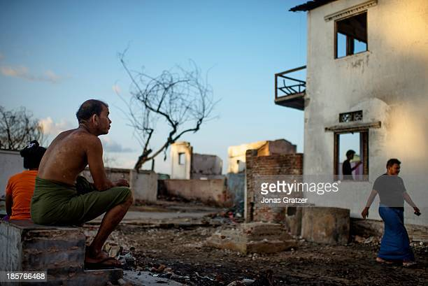 Muslim man sits with his wife on top of a step that once belonged to their home after it had been destroyed in the violence that was led against...