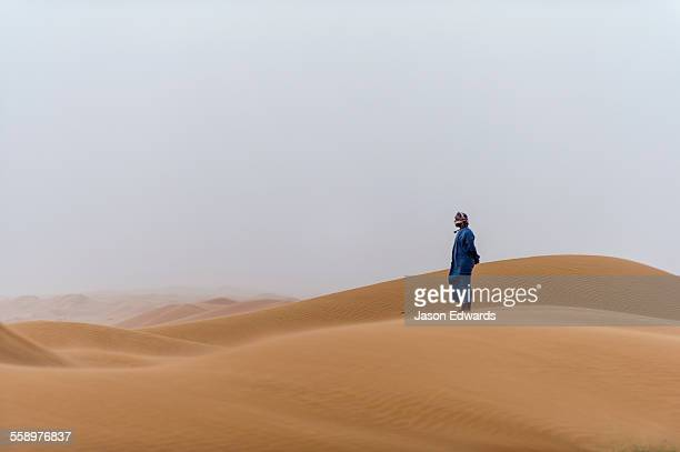 A Muslim man standing on a sand dune at sunset wearing a traditional dishdasha and masar.