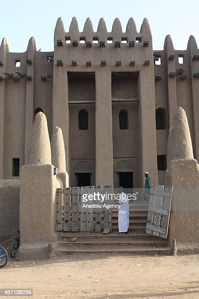 A muslim man stands in front of the entrance door of the mud mosque in Djenne Mali on October 6 2014 The Great Mosque of Djenne is the largest mud...