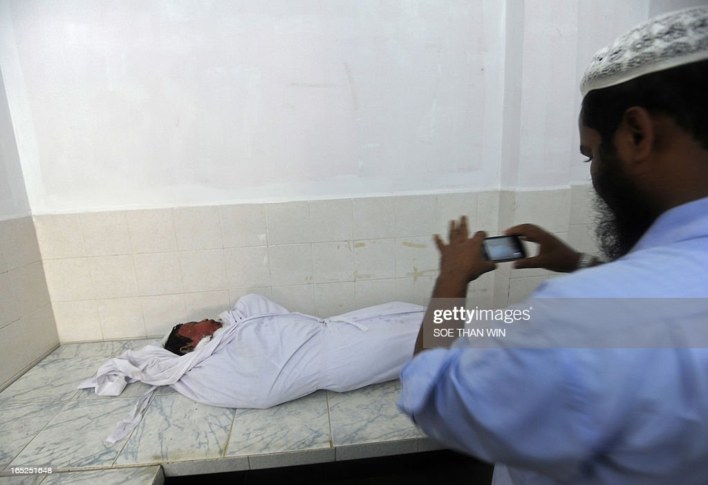 A Muslim man takes a photograph of one of the victims killed in a fire at an Islamic school, at Yay Way Islamic cemetery in Yangon on April 2, 2013. A fire killed 13 students at a Muslim school in Myanmar's main city on April 2, police said, raising tensions in the wake of sectarian clashes despite police assurances that the blaze was accidental. AFP PHOTO/ Soe Than WIN
