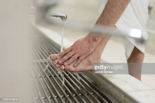muslim man taking ablution for prayer washing foot - foot worship stock pictures, royalty-free photos & images