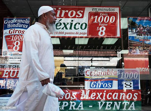 Muslim man walks by a store specializing in phone calls and travel to Latin America in the ethnically diverse neighborhood of Queens on August 29...