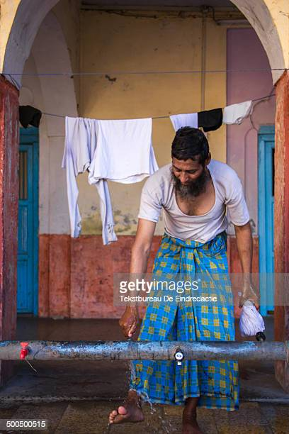 Muslim man washing his feet and laundry at the mosque before the afternoon prayer. New Delhi, capital city of India.