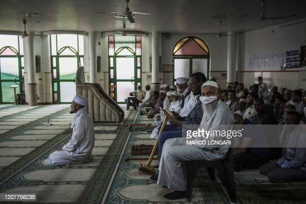 A Muslim man wearing a makeshift mask as a preventive measure against the COVID19 coronavirus sits with other worshippers the beginning of the Friday...