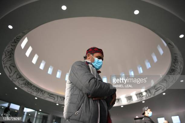 Muslim man wears a facemask as he attends socially distanced Friday Prayers at the Baitul Futuh Mosque of the Ahmadiyya Muslim Community in south...