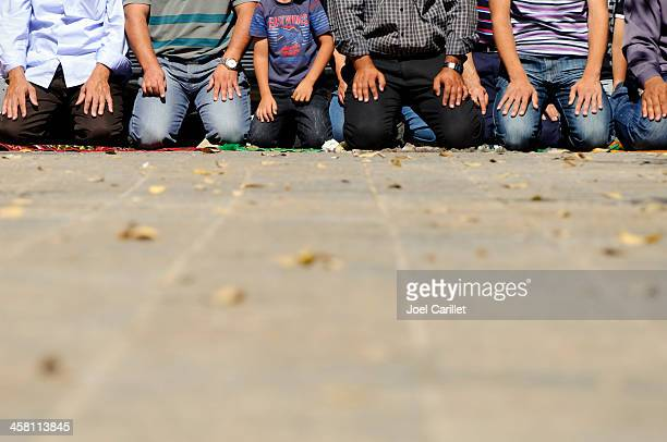 muslims praying - knees together stock photos and pictures