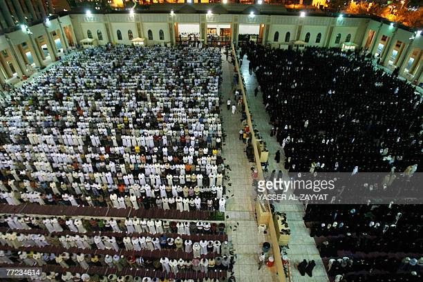 Muslim men and women separated by a wall pray in Kuwait City's Grand Mosque just before daybreak early 09 October 2007 during Laylat alQadr which...