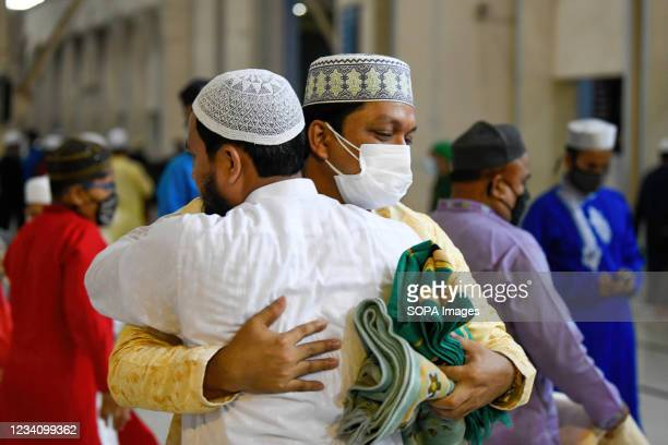 Muslim men are seen hugging after Eid al-Adha prayers at Baitul Mukarram National Mosque in Dhaka.