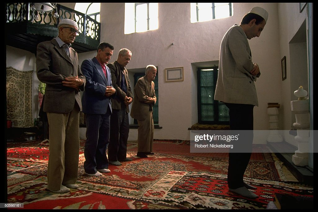 Muslim men at prayer (attended by 5) at : News Photo