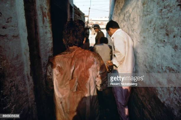 Muslim men attacked and seriously wounded by rampaging Hindu mobs are helped by police officers December 12 1992 in Seelampur India The attacks on...