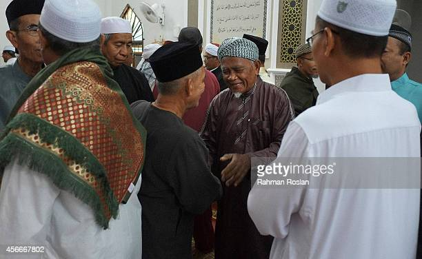 Muslim men greet and wish each other well after the Eid AlAdha morning prayers on October 5 2014 in Duyong Malacca Malaysia Muslims worldwide...