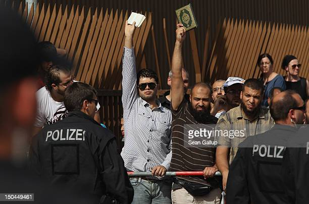 Muslim men hold up copies of the Koran in response to supporters of the pro Deutschland rightwing antiIslam group displaying a caricature of the...
