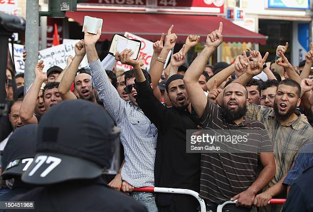 Muslim men hold up copies of the Koran to protest the arrival of supporters of the pro Deutschland rightwing antiIslam group outside the Dar Assalam...