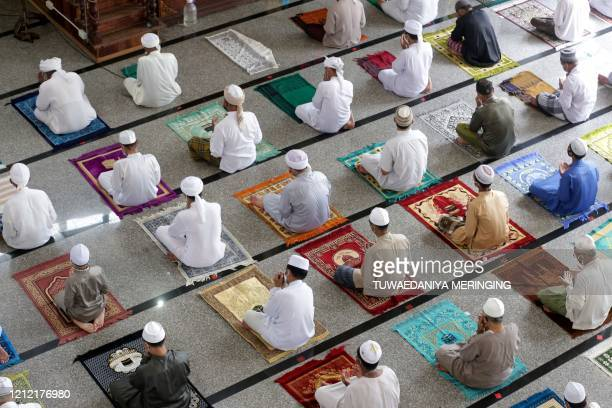 TOPSHOT Muslim men practise social distancing as a preventive measure against the spread of the COVID19 novel coronavirus as they take part in Friday...