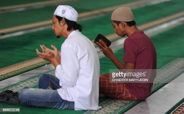 Muslim men pray at the Baiturrahman mosque in Banda Aceh Aceh province on May 27 on the first day of the fasting in the Muslim holy month of Ramadan...