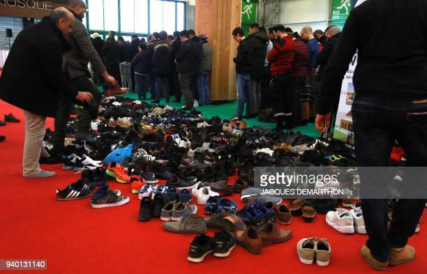 Muslim men remove their shoes before prayer during the 35th annual meeting of the French Muslim community on March 30 2018 at Le Bourget north of...