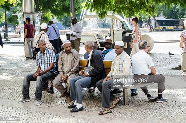 Muslim men sitting on a park bench and discussing