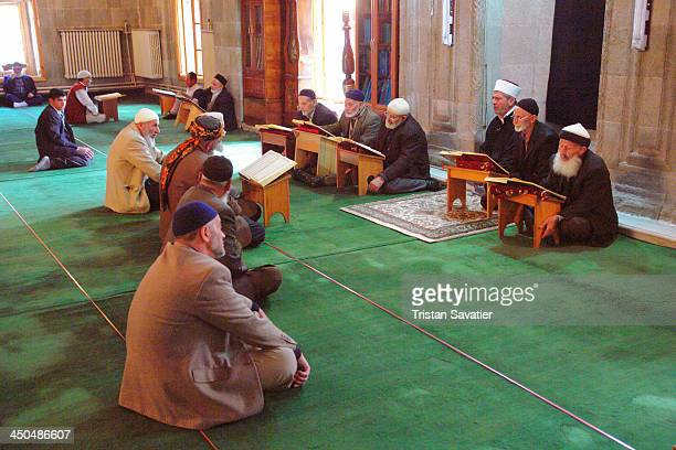 CONTENT] Muslim men Studying the Quran in a Mosque in Erzurum people sitting crosslegged Imams Islam religion faith quraan koran reading Holy book...