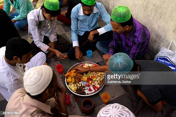 Muslim men take food after breaking the daylong fast on the eve of EidulFitr at the end of the month of Ramadan in Kolkata