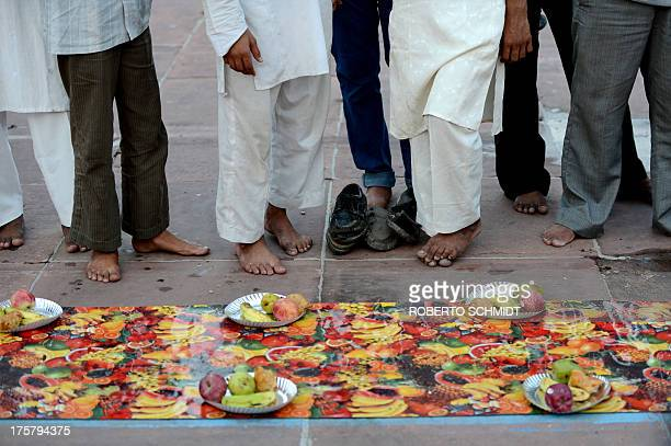 Muslim men wait to break their fast for the last time during the holy month of Ramadan at the Jama Masjid mosque in New Delhi on August 8 2013...