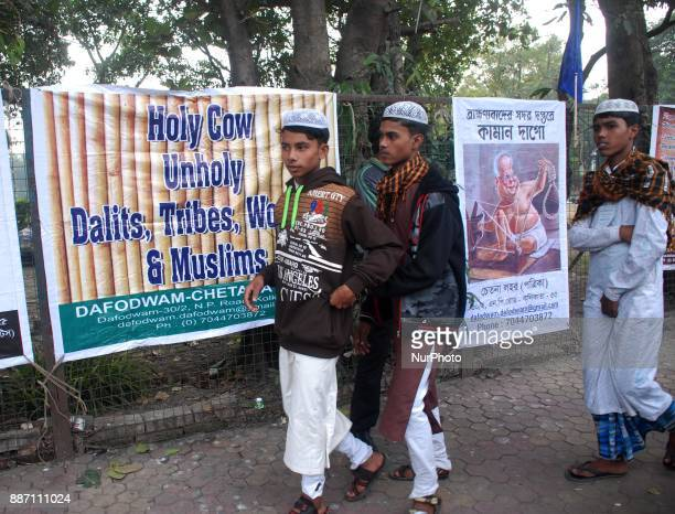 Muslim men walk past in front of the poster during the protest against Bharatiya Janata Party on the occasion of 25th anniversary of the demolition...
