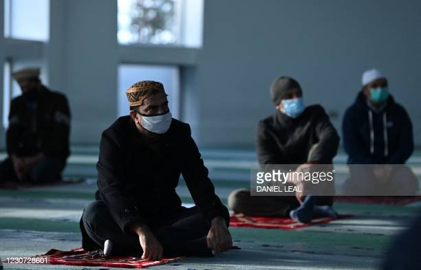Muslim men wear facemasks as they attend socially distanced Friday Prayers at the Baitul Futuh Mosque of the Ahmadiyya Muslim Community in south west...