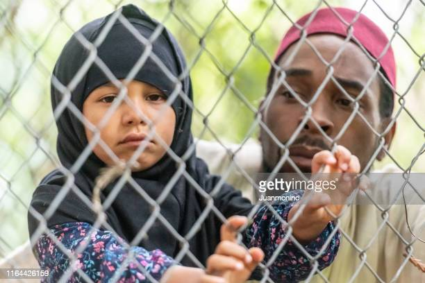muslim mid adult black man holding his daughter looking through a fence - lampedusa stock pictures, royalty-free photos & images