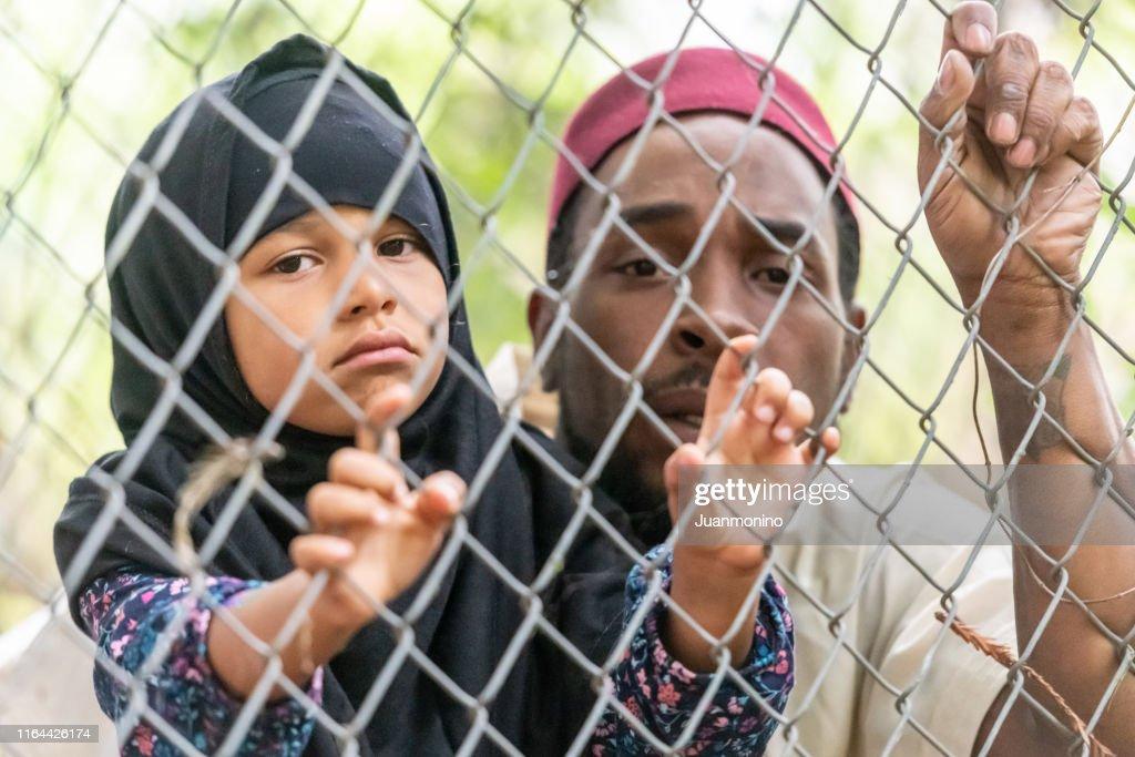 イスラム教徒の中年の黒人男性がフェンスを通して見て娘を抱いている : ストックフォト
