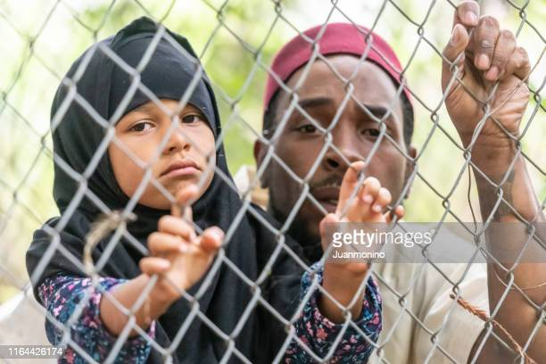 muslim mid adult black man holding his daughter looking through a fence - refugee camp stock pictures, royalty-free photos & images