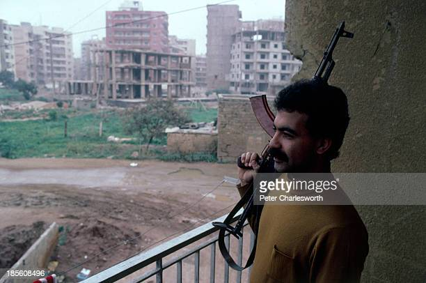 A muslim militia fighter belonging to the Amal Shi'ite faction with an AK47 semiautomatic rifle guards a front line position in the southern suburbs...
