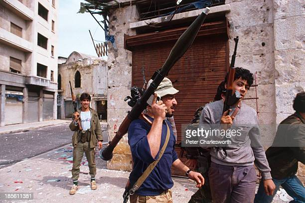 Muslim militia fighters belonging to the Amal Shi'ite faction with their AK47 semiautomatic rifles and a rocket propelled grenade launcher move to a...