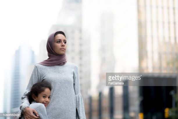 muslim mother and child hug in the city - emigration and immigration stock pictures, royalty-free photos & images